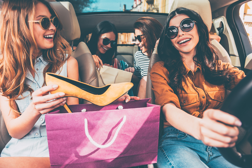 A group of girl friends are in their car, looking at all they bought from the New Braunfels shops.