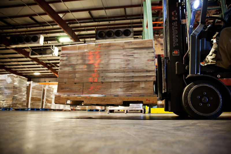 The inside of the Northern Refrigerated Transportation and Poppy State Express warehouse and crossdock, featuring pallets on a forklift.