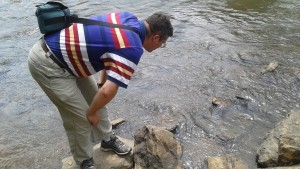 Dr. Campbell observes the river, finding several dead fish.