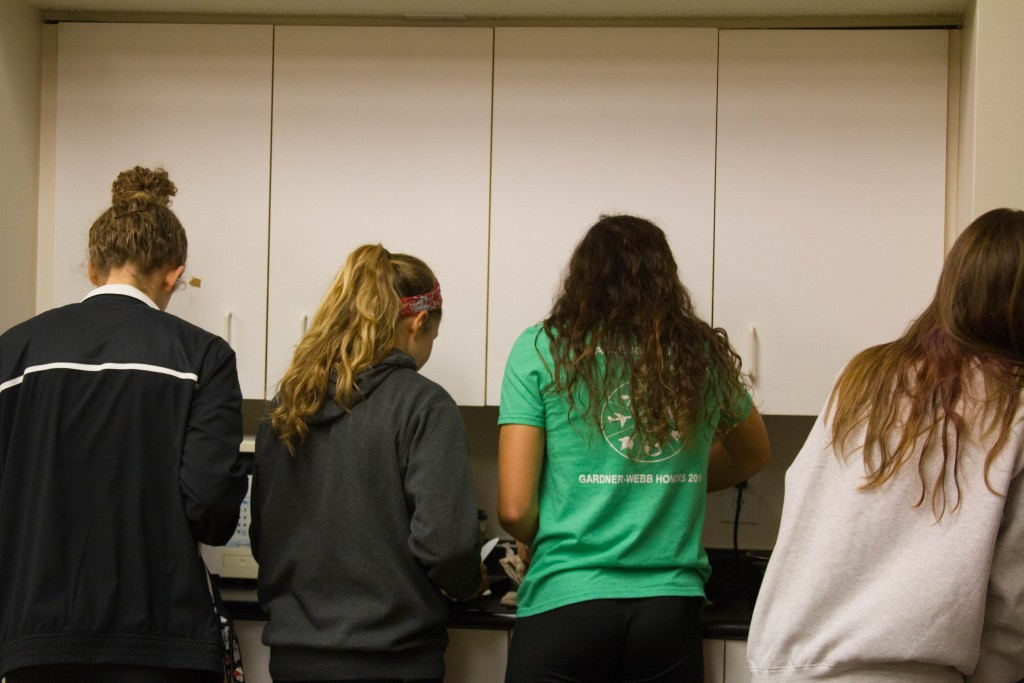 FCA leaders gather around skillets to cook pancakes for students who came.