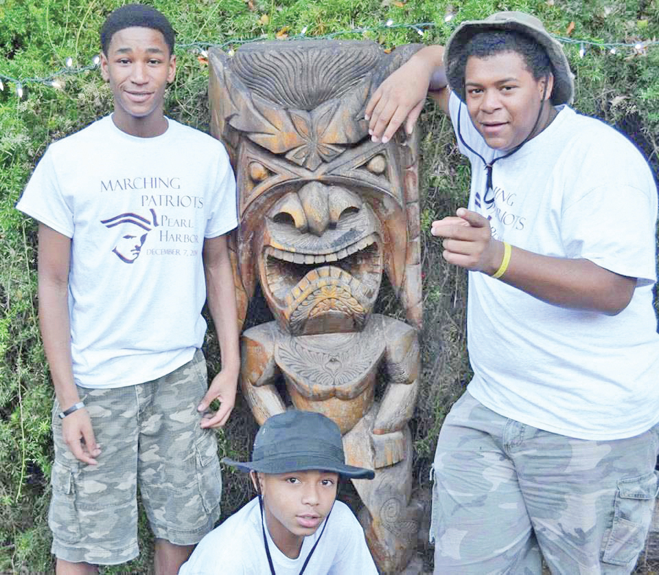 Band students visiting Tiki Statue in Hawaii from left: Zaire Penn, Raekwon Manns (stooping down), and Camry Campbell