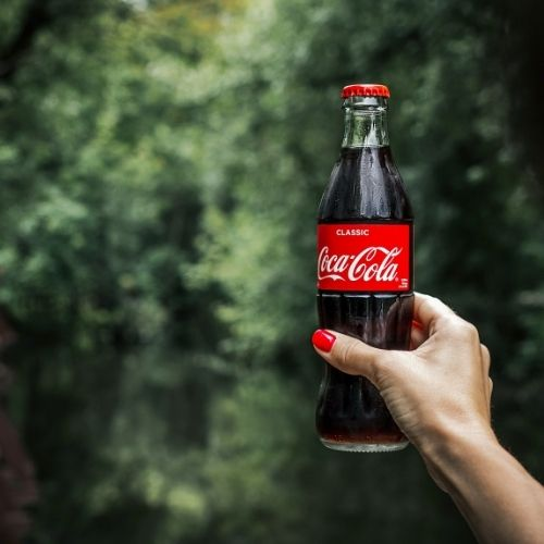 woman with painted nails holds bottle of coke