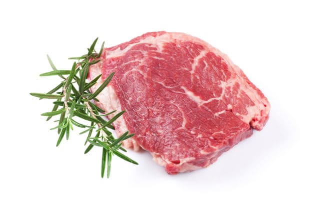 Raw beef steak and rosemary. Isolated on white background