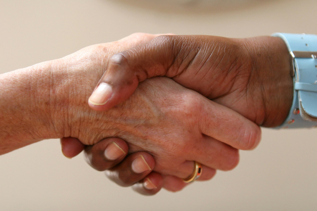 Helping hand shakes another hand as part of an agreement