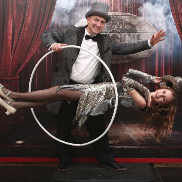 Male magician in top hat with female assistant magically suspended within a hula hoop, several feet off ground