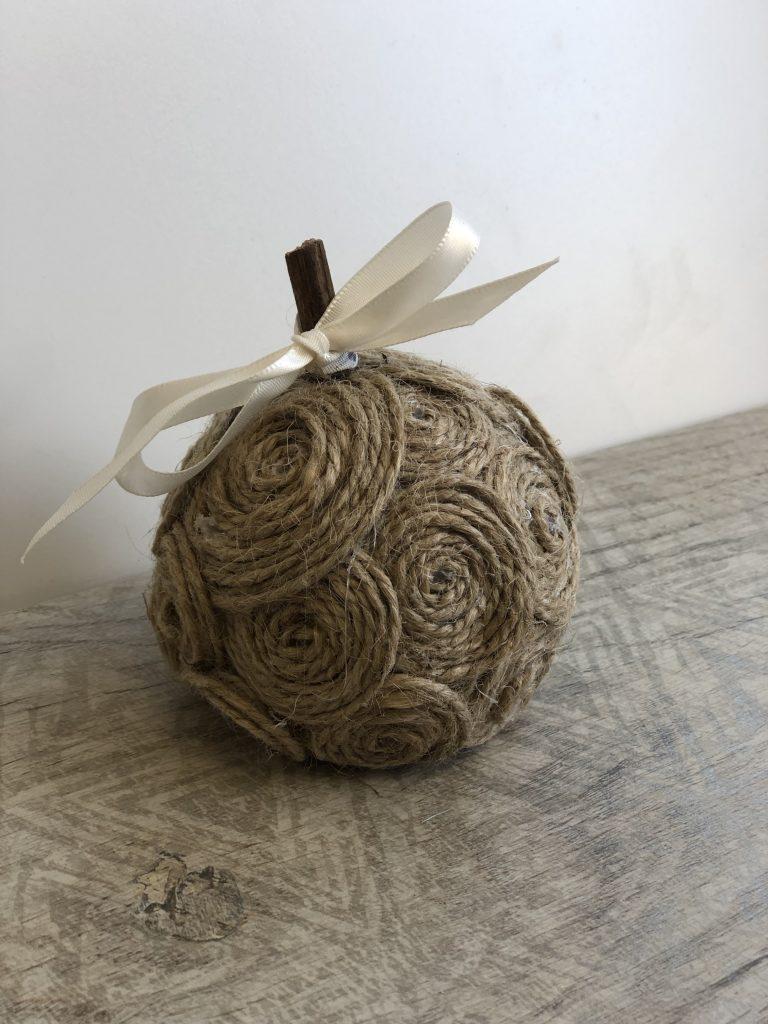 Stunning elegant tan, mini pumpkin made out of yarn or twine pumpkin . Simple satin bow. Beautiful easy fall diy.