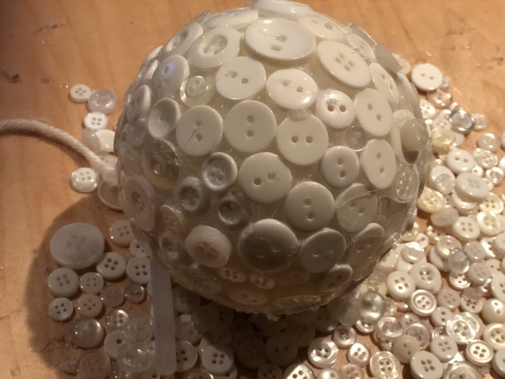 White buttons placed on styrofoam ball .Christmas tree ornament craft diy
