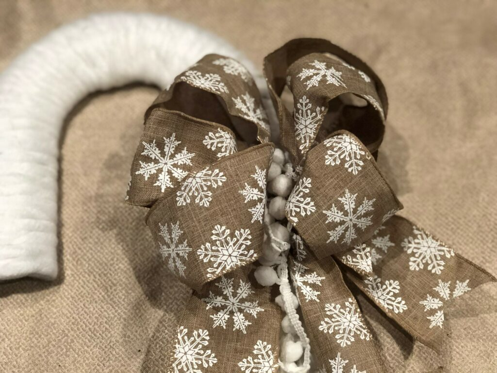 Simple Folded Easy Bow with snowflake charms to decorate your Christmas Wreath. Candy Cane Rustic Christmas Wreath diy