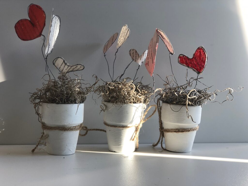 Book pages heart garden to decorate your window for Valentines Day. Super cute budget friendly decor.