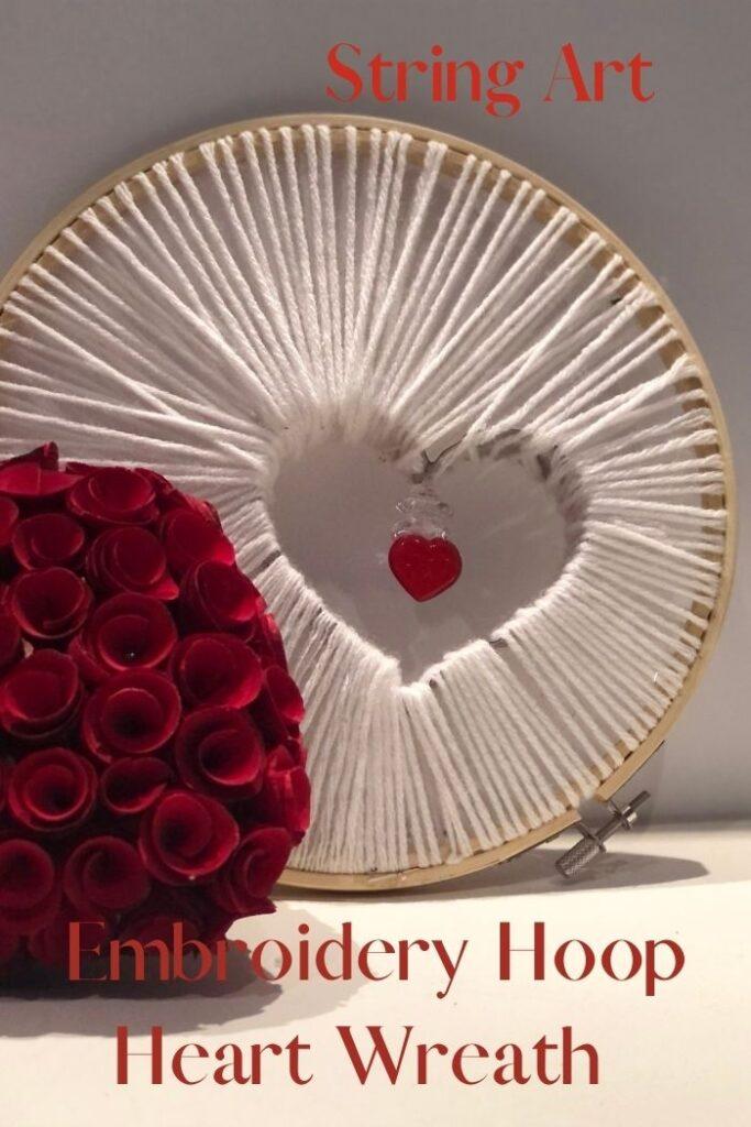 Embroidery hoop string art wreath with embellishments ready for Valentine's Day. Easy evergreen diy wreath. Yarn wreath