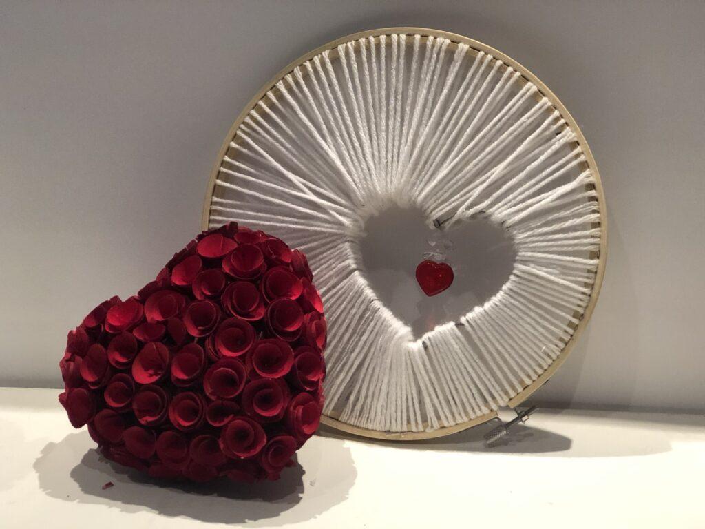 Embroidery hoop string art heart wreath with embellishments ready for Valentine's decor. Evergreen yarn wreath diy