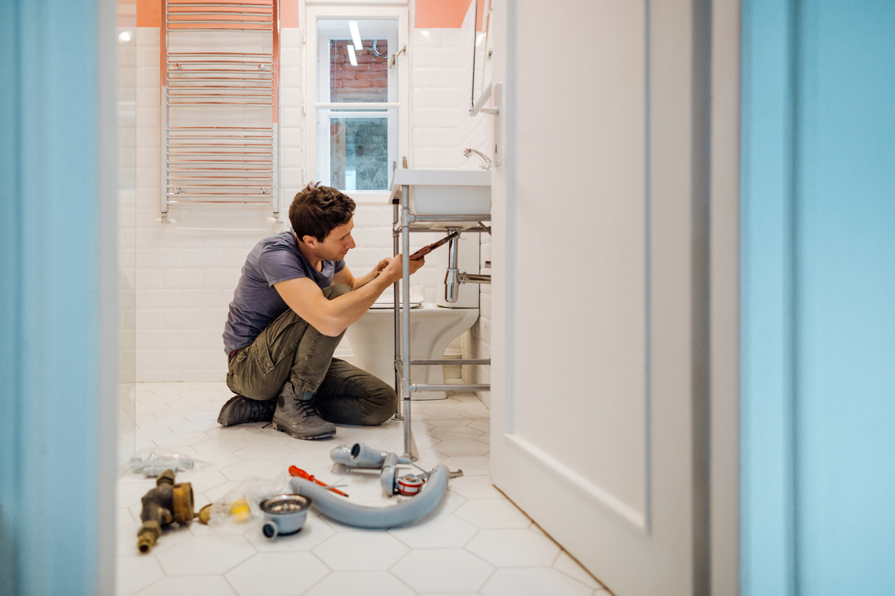 a plumber fixing plumbing damage that is covered by insurance
