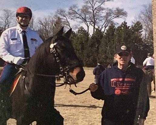 A veteran on a horse being lead by a volunteer