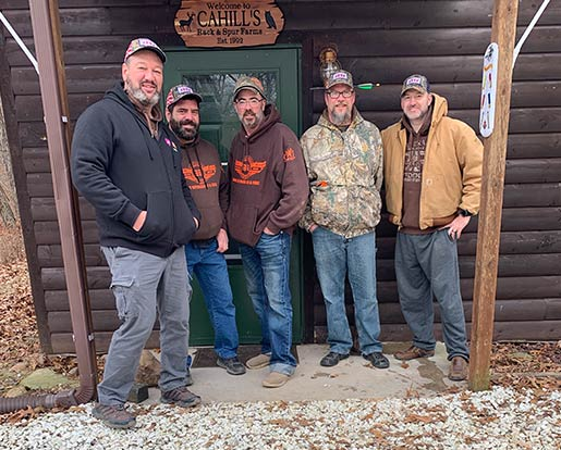 A group of veterans outside a hunting lodge