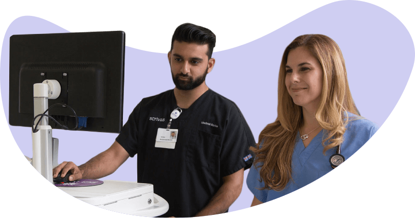 Scribe updating EMR in front of computer to reduce physician burden