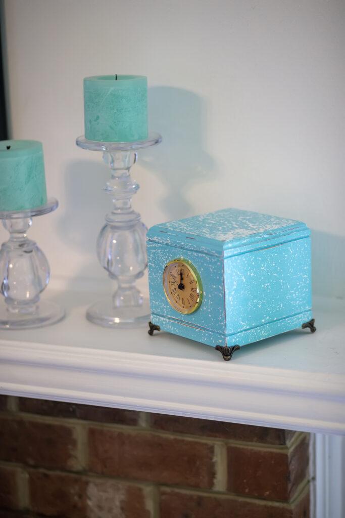 Hardwood pet urn with blue salt wash finish, clock, and brass corner feet.