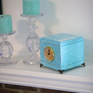 Hardwood pet urn with blue salt wash finish, clock, and brass corner feet.