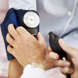 Pair of Human Hands Checking the Blood Pressure of a Patient --- Image by © Royalty-Free/Corbis