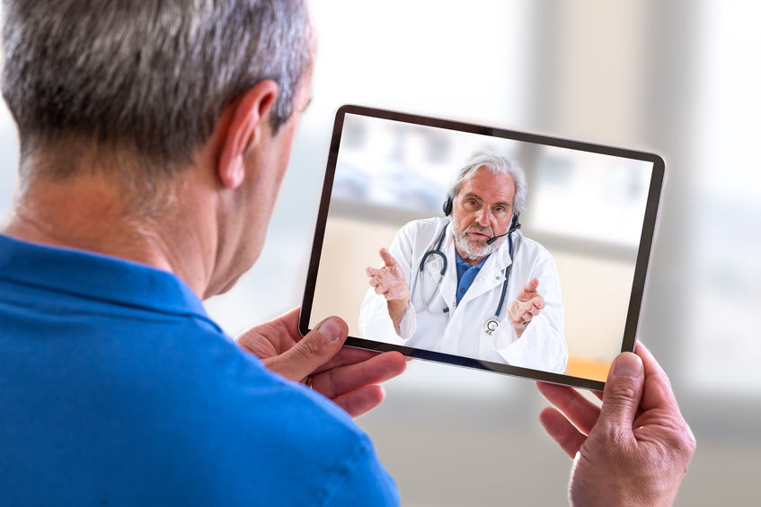 Remote consultation- Doctor sitting at hospital, with laptop, having an online call with patient showing tablet device