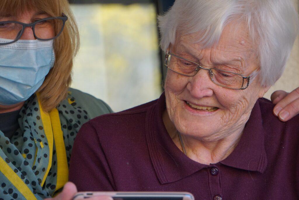 caregiver helps elderly woman