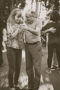 Elderly man dances with female caregiver