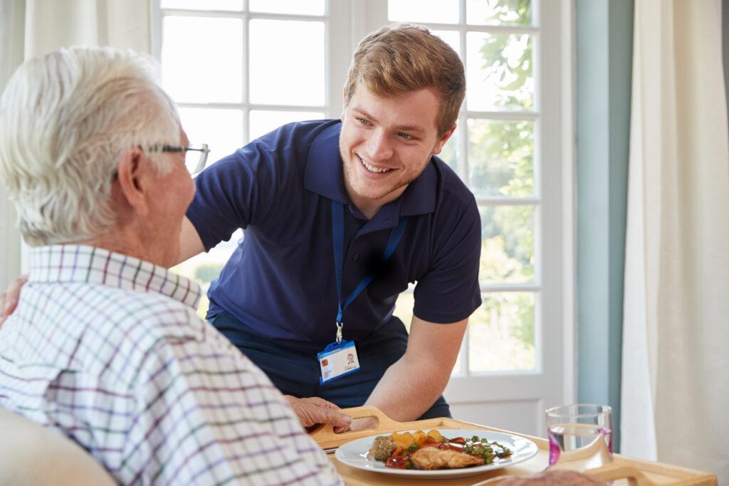 male caregiver smiles at senior mane