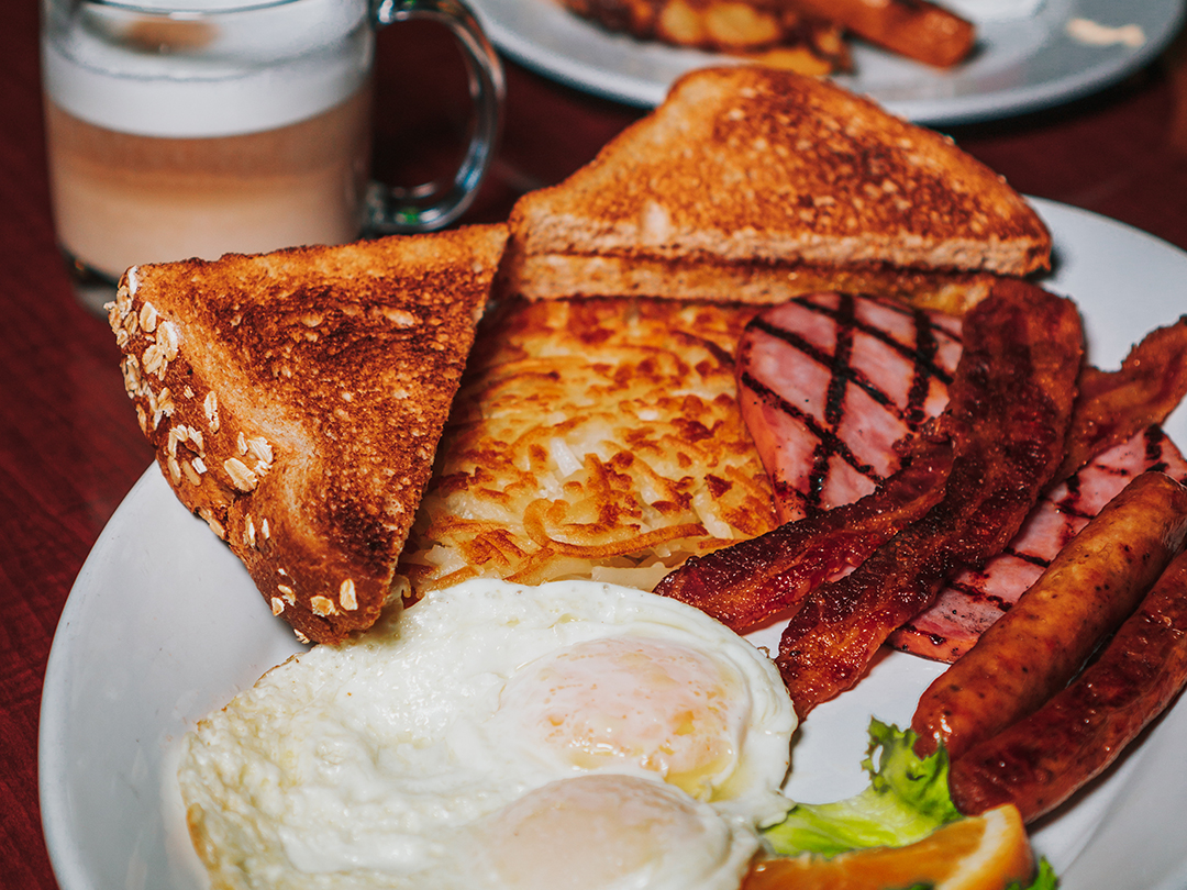 Breakfast with hash browns, ham, sausage, bacon, eggs and toast