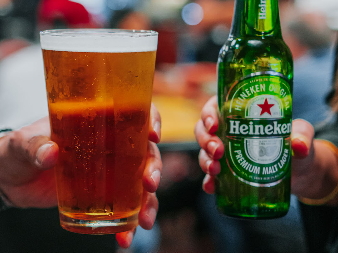 Two people's hands, one holding a glass of beer, the other holding a bottle of Heineken beer.