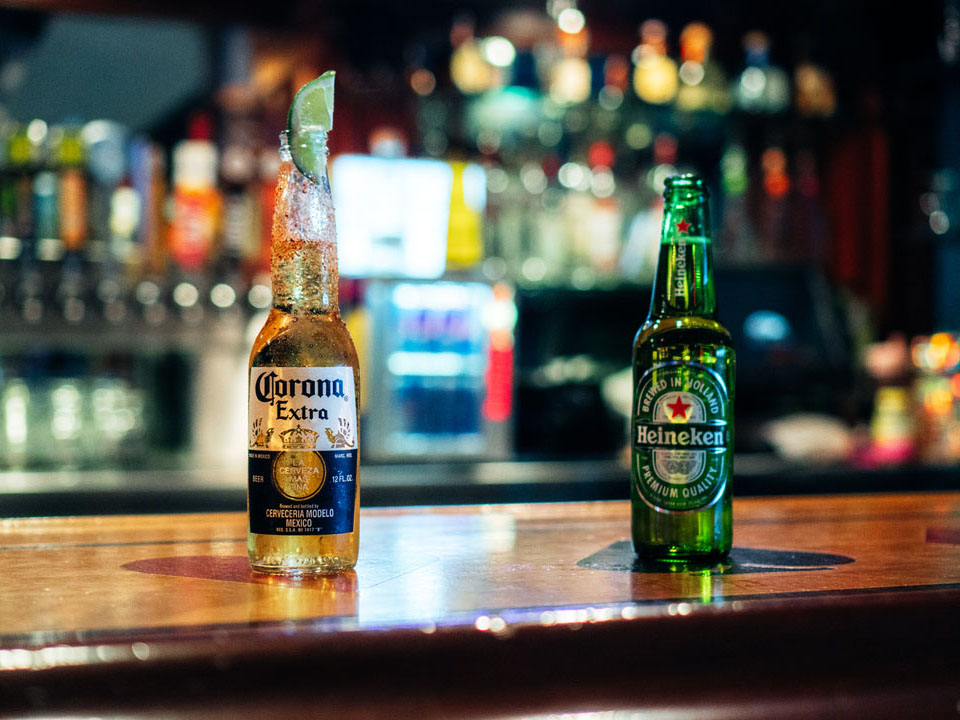 A Corona Extra and Heineken beer on a bar top.