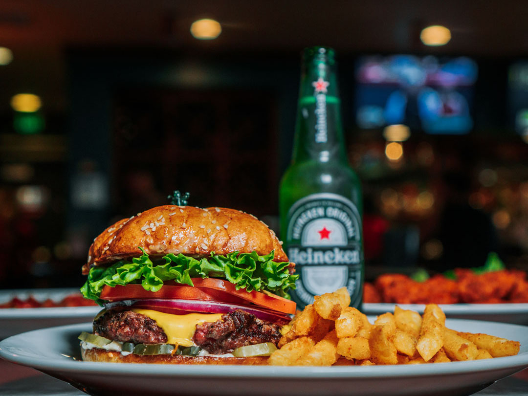 Burger and fries with a beer in the background