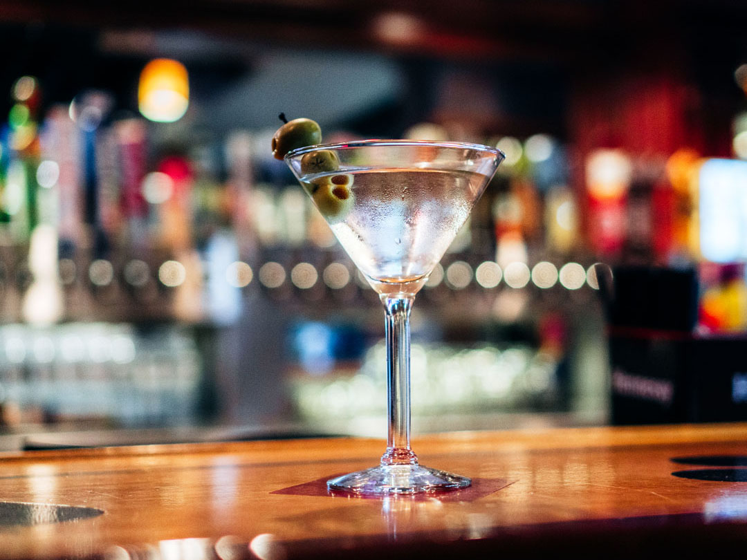 Martini glass on the bar top with olives.