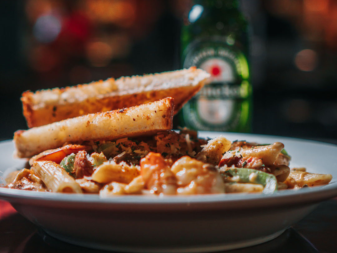 A bowl of pasta with bread and beer.