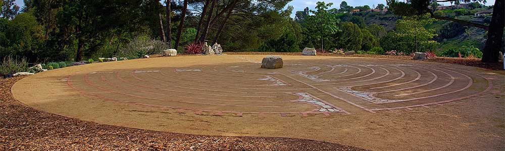 The labyrinth with center stone surrounded by stones and trees