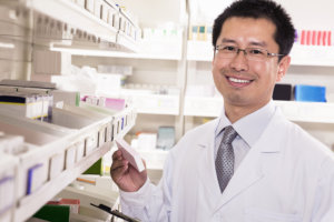 Pharmacist taking down and examining prescription medication in a pharmacy