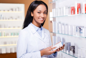Beautiful young African woman in lab coat holding container with some medicine