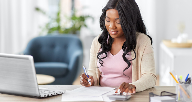 Woman uses calculator to prepare invoice for freelance clients