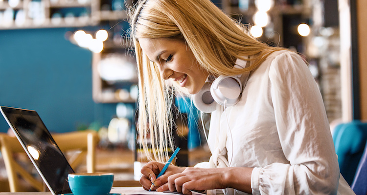A woman does freelance work on a laptop from a coffeeshop