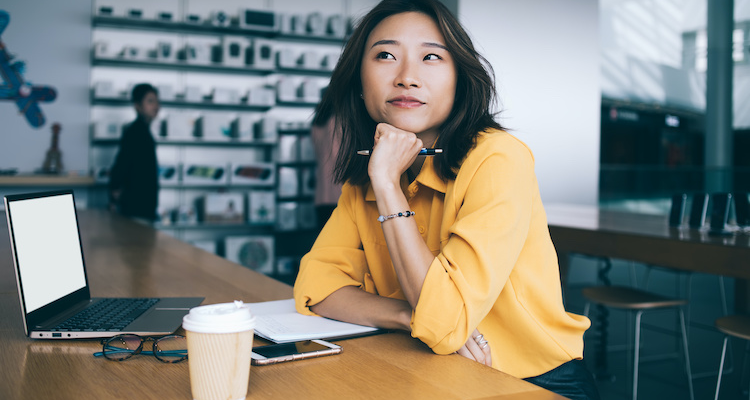 Woman at desk with laptop considers the traits of successful freelancers