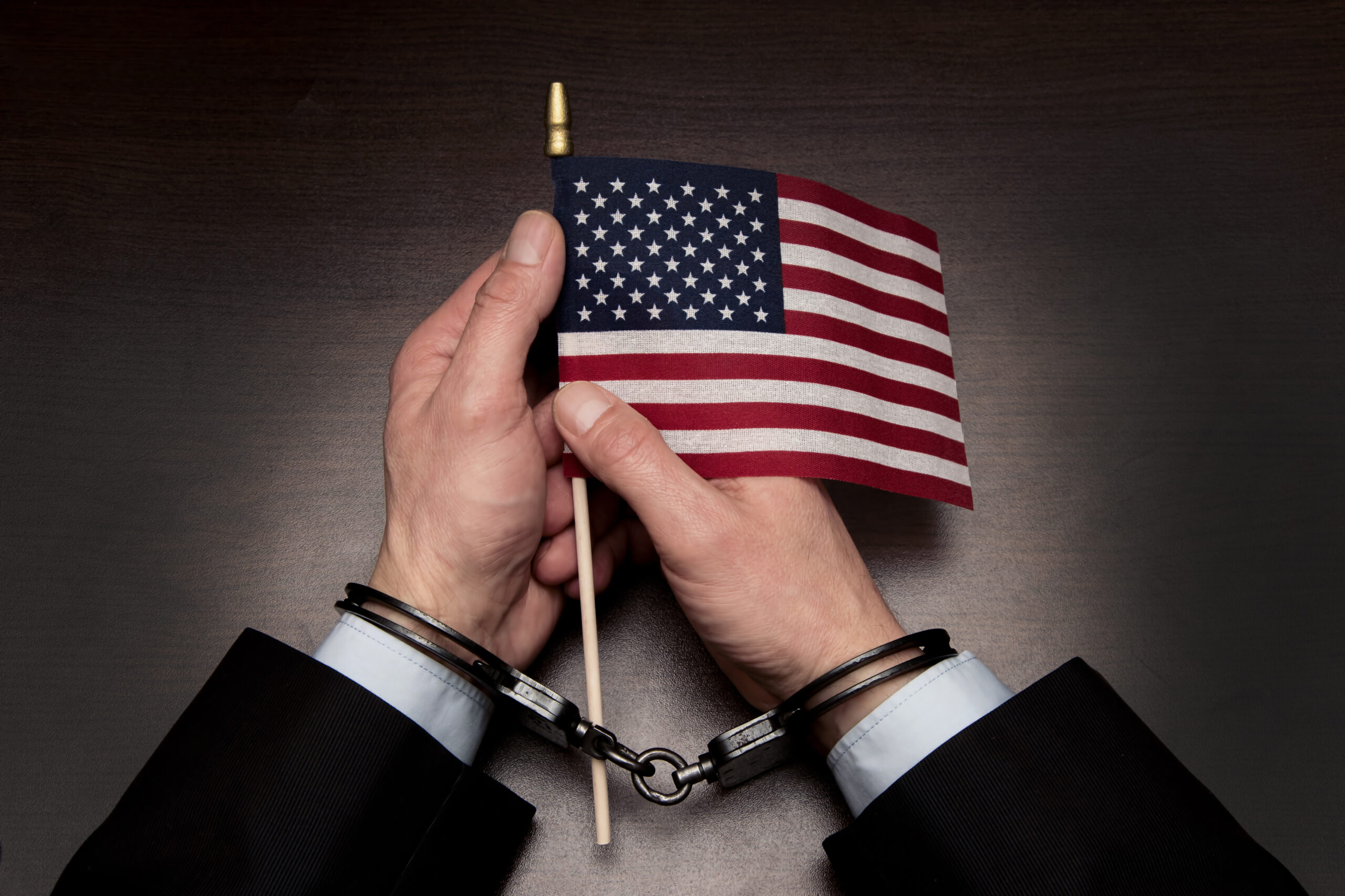 Men's hands in handcuffs hold the American flag in their hands. Concept: American prisoner, imaginary freedom, deportation from the country, persona non grata
