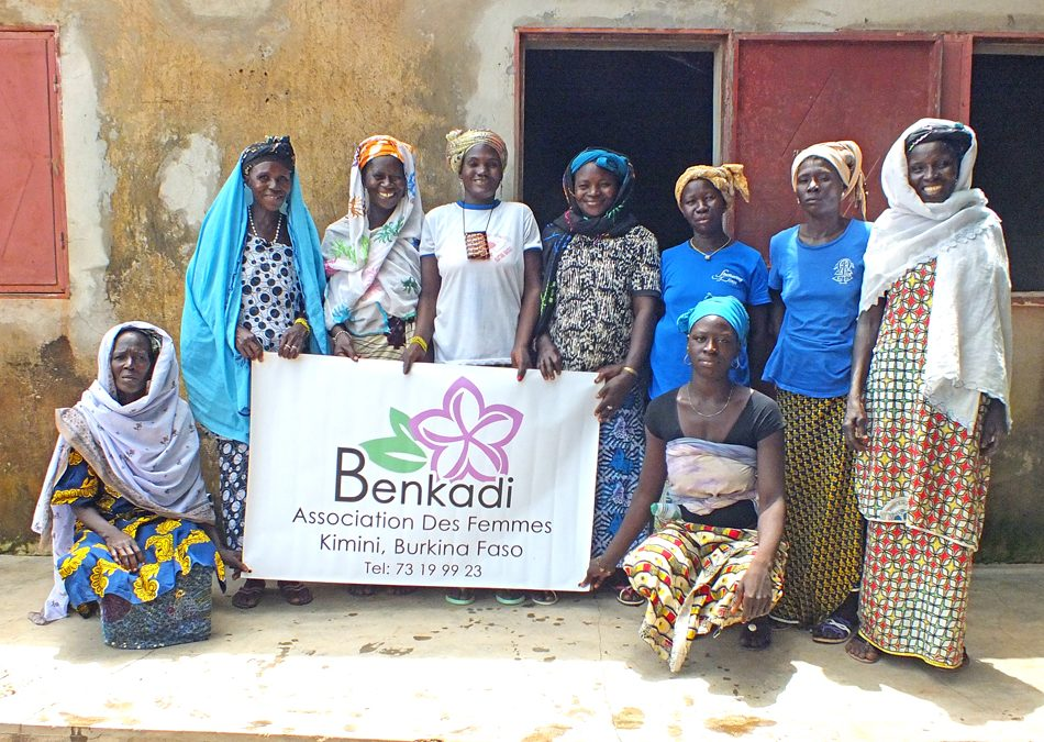 A group of 9 women stand together proudly, holding up a banner for their new business called Benkadi in Burkina Faso