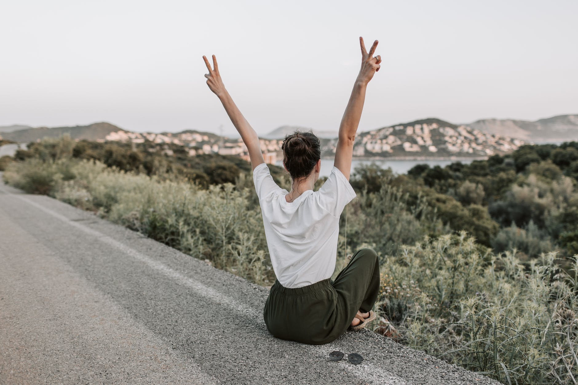 woman sitting on the road making a peace sign