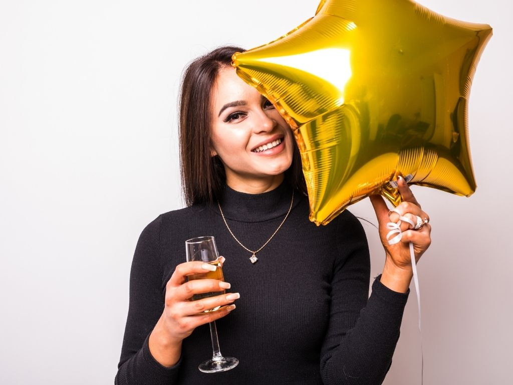 empath woman in black dress with gold star shaped balloon drinking champagne