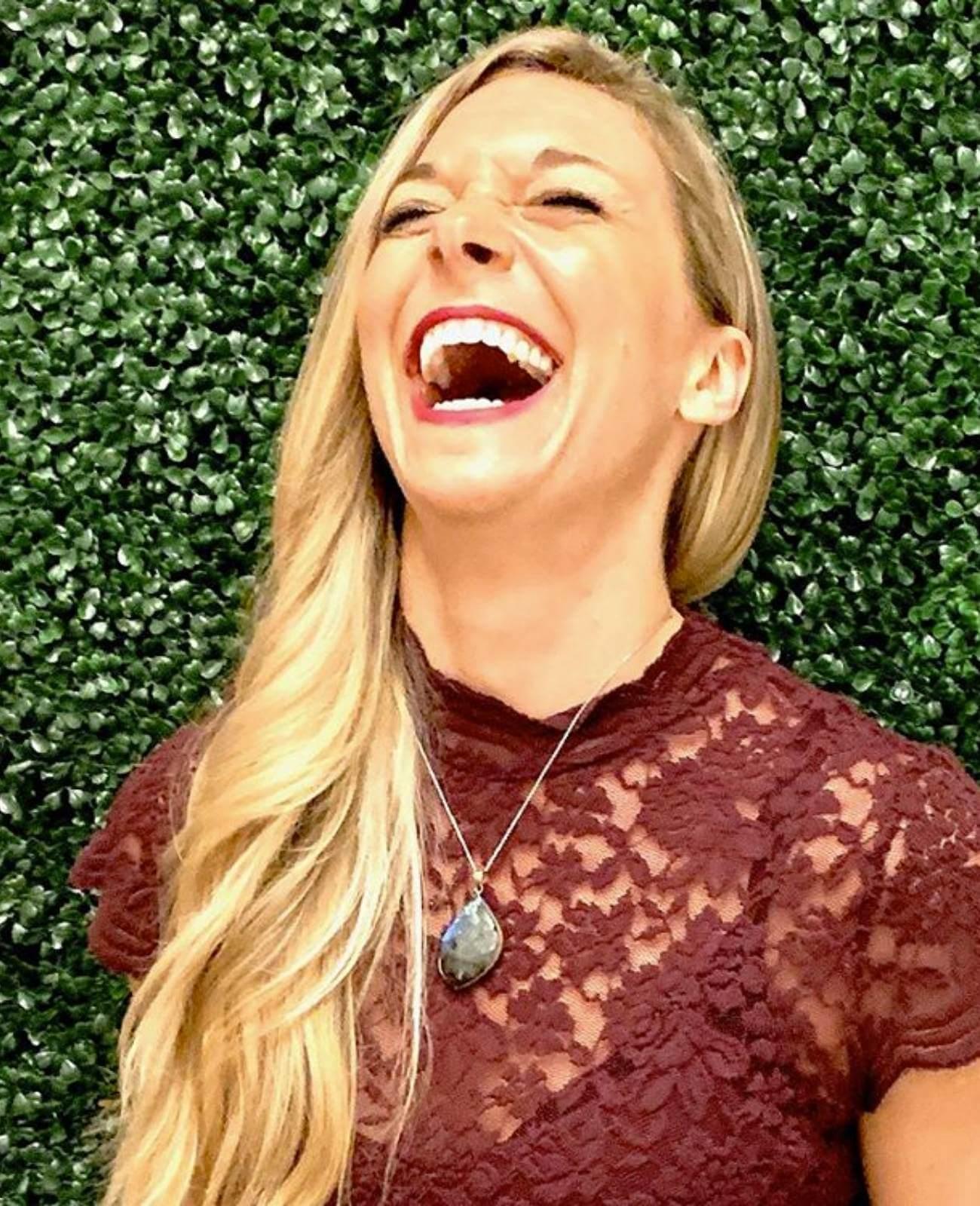 Blonde woman in fancy maroon shirt laughing
