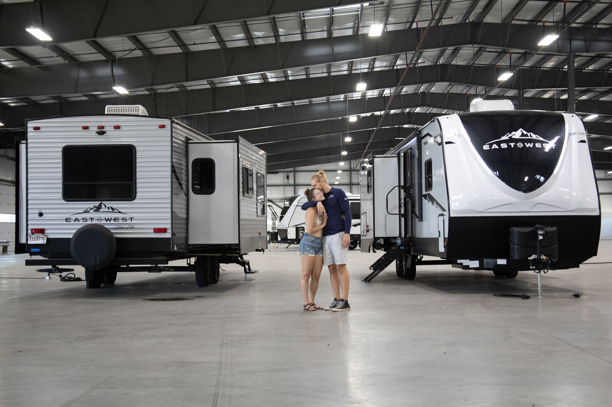 two people standing next to RVs