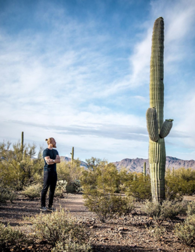 Man standing next to very tall cactus