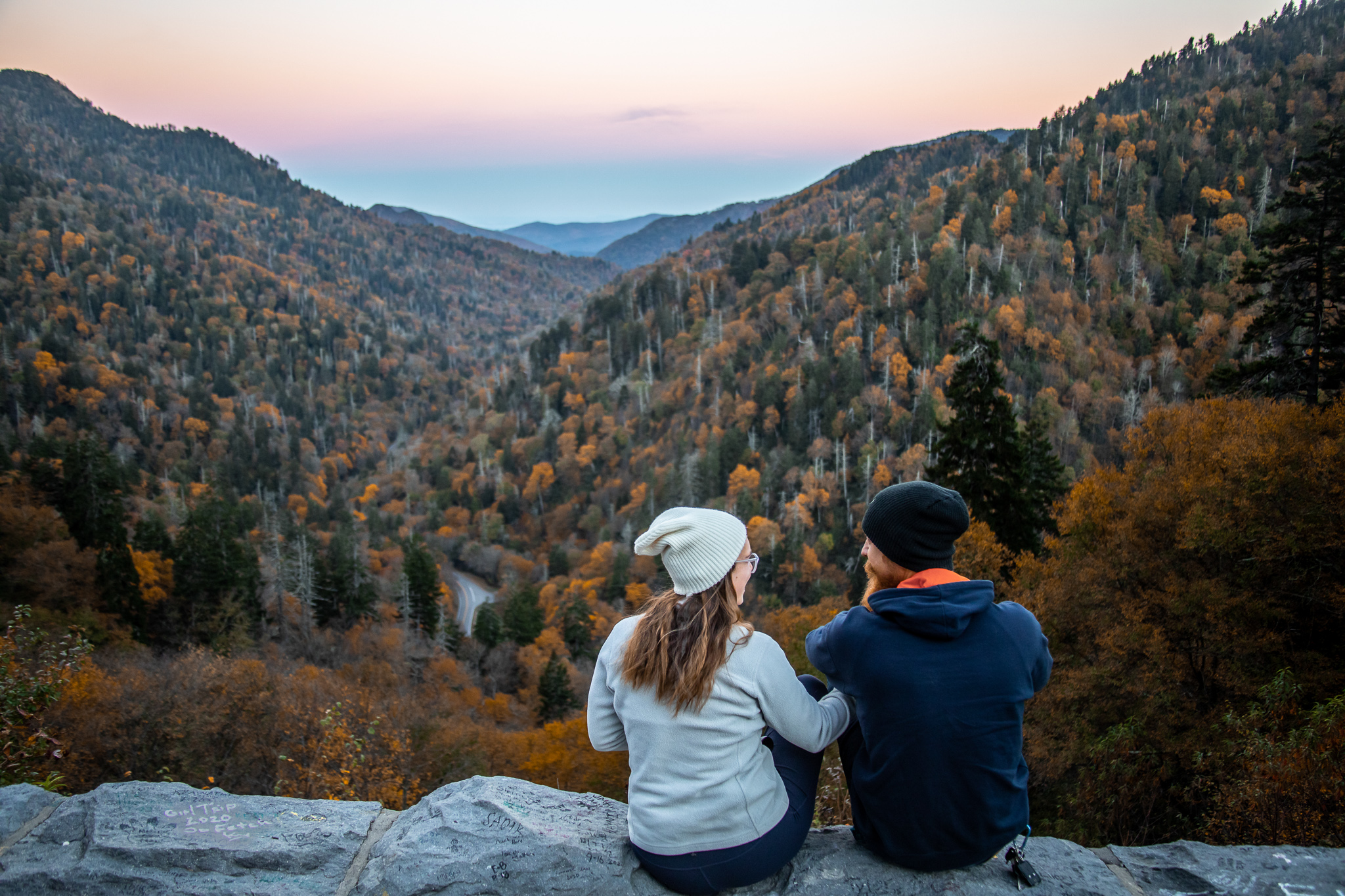 Two people sitting on a mountain