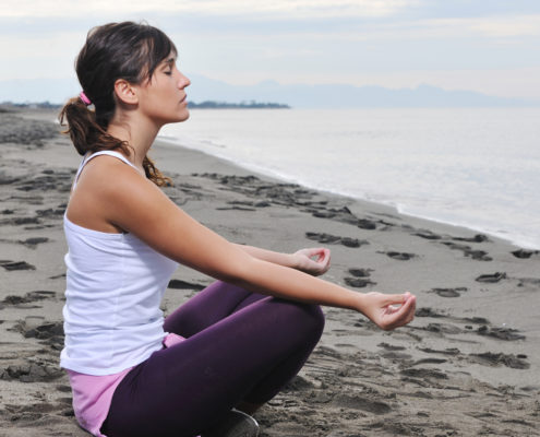 woman yoga beach deep breathing exercises