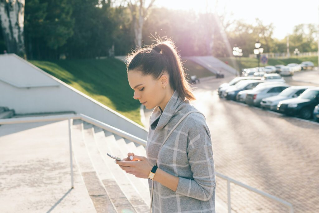 Attractive woman with brown hair climbs the stairs in the city and uses a mobile phone on a sunny day