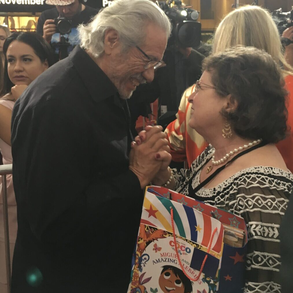 """Photo Courtesy of Justin Daniel Ashford</br> <span style=""""color:#EF4E24"""">Edward James Olmos and Roni <br>Background - Patty Rodríguez – <a href=""""https://lillibros.com/"""" target=""""_blank"""" rel=""""noopener noreferrer""""><b>Lil' Libros</b></span></a>"""