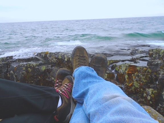 2 pairs of feet on the shoreline